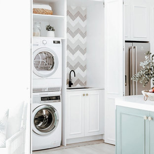 Laundry closet - small single-wall light wood floor and gray floor laundry closet idea in Dallas with an undermount sink, white cabinets, quartzite countertops, gray backsplash, ceramic backsplash, white walls, a stacked washer/dryer and white countertops