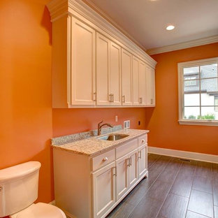 This is an example of a large classic galley utility room in Other with a submerged sink, white cabinets, granite worktops, orange walls, medium hardwood flooring and a side by side washer and dryer.