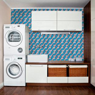 Idéer för en mellanstor modern bruna u-formad tvättstuga enbart för tvätt, med en enkel diskho, träbänkskiva, bruna skåp, blå väggar, plywoodgolv, en tvättpelare, brunt golv och luckor med profilerade fronter