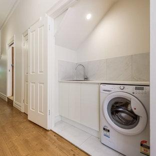 Ispirazione per una piccola lavanderia multiuso moderna con lavello da incasso, ante a persiana, ante bianche, top in granito, pareti bianche, pavimento con piastrelle in ceramica, lavasciuga, pavimento bianco e top bianco
