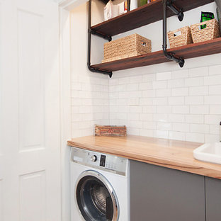 Idee per una piccola lavanderia multiuso moderna con ante lisce, ante grigie, top in legno, pareti bianche, lavello stile country, pavimento in legno massello medio e lavasciuga