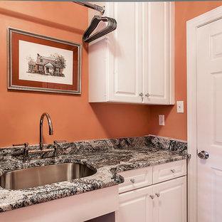 Bild på en liten vintage linjär tvättstuga enbart för tvätt, med en undermonterad diskho, skåp i shakerstil, vita skåp, granitbänkskiva, orange väggar, klinkergolv i porslin och en tvättmaskin och torktumlare bredvid varandra