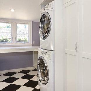 Inredning av en klassisk mellanstor u-formad tvättstuga enbart för tvätt, med en undermonterad diskho, skåp i shakerstil, vita skåp, bänkskiva i kvarts, lila väggar, klinkergolv i keramik, en tvättpelare och svart golv