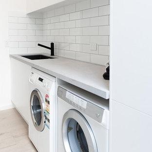 Esempio di una sala lavanderia nordica di medie dimensioni con lavello sottopiano, nessun'anta, ante bianche, top in quarzo composito, pareti bianche, parquet chiaro, lavatrice e asciugatrice affiancate e top grigio