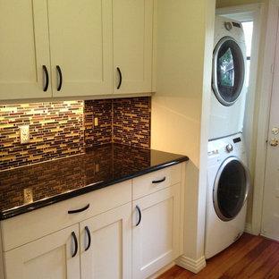 Inspiration för små eklektiska l-formade tvättstugor, med skåp i shakerstil, vita skåp, granitbänkskiva, mellanmörkt trägolv, en tvättpelare och beige väggar
