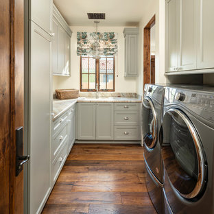 Inspiration for a timeless u-shaped medium tone wood floor and brown floor dedicated laundry room remodel in Phoenix with an undermount sink, recessed-panel cabinets, gray cabinets, a side-by-side washer/dryer, beige countertops and white walls