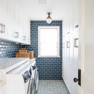 This is an example of a country galley dedicated laundry room in Los Angeles with recessed-panel cabinets, white cabinets, blue walls, a side-by-side washer and dryer, blue floor and white benchtop.