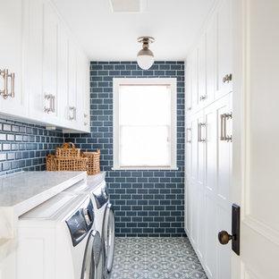 На фото: отдельная, параллельная прачечная в стиле кантри с фасадами с утопленной филенкой, белыми фасадами, синими стенами, со стиральной и сушильной машиной рядом, синим полом и белой столешницей с