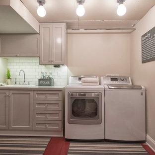 Foto di una sala lavanderia stile marino di medie dimensioni con lavello da incasso, ante in stile shaker, ante grigie, top in laminato, pareti grigie, pavimento in cemento e lavatrice e asciugatrice affiancate