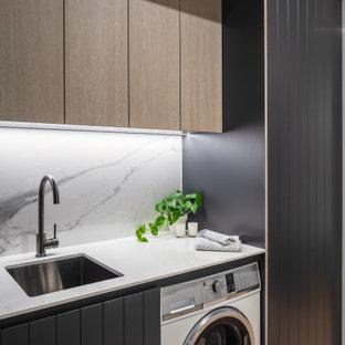 Cette photo montre une petit buanderie linéaire moderne multi-usage avec un évier encastré et une crédence en carreau de porcelaine.