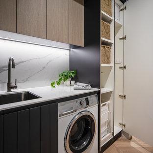 Ispirazione per una piccola lavanderia multiuso moderna con lavello sottopiano e paraspruzzi in gres porcellanato