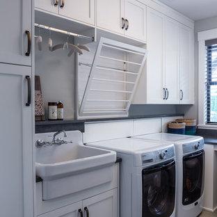 Idées déco pour une buanderie classique en L dédiée avec un placard à porte shaker, des portes de placard blanches, un mur gris, des machines côte à côte, un sol gris, un plan de travail gris et un évier posé.