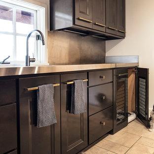 Inspiration för en stor funkis linjär tvättstuga enbart för tvätt, med en rustik diskho, bruna skåp, bänkskiva i rostfritt stål och beige väggar