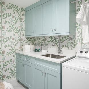 Exempel på en mellanstor maritim vita linjär vitt tvättstuga enbart för tvätt, med en undermonterad diskho, skåp i shakerstil, blå skåp, bänkskiva i kvarts, klinkergolv i porslin, en tvättmaskin och torktumlare bredvid varandra och vitt golv
