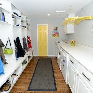 Foto de lavadero multiusos y de galera, clásico, con fregadero bajoencimera, armarios con paneles con relieve, puertas de armario blancas, paredes grises, suelo de madera en tonos medios y lavadora y secadora juntas