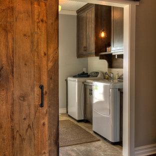 Inredning av en rustik mellanstor linjär tvättstuga enbart för tvätt, med en tvättmaskin och torktumlare bredvid varandra, klinkergolv i porslin, beiget golv, skåp i shakerstil och skåp i mörkt trä