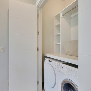 Inspiration for a mid-sized contemporary single-wall laundry cupboard in Calgary with flat-panel cabinets, white cabinets, solid surface benchtops, grey walls, porcelain floors, a side-by-side washer and dryer and grey floor.