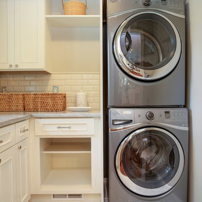 Small elegant l-shaped dedicated laundry room photo in DC Metro with white cabinets, marble countertops and a stacked washer/dryer