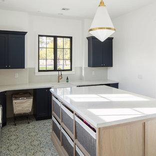 Esempio di una grande sala lavanderia country con lavello stile country, ante in stile shaker, ante blu, top in quarzo composito, pareti bianche, lavatrice e asciugatrice affiancate, top bianco e pavimento multicolore