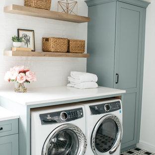 Idéer för lantliga linjära vitt tvättstugor enbart för tvätt, med skåp i shakerstil, blå skåp, vita väggar, en tvättmaskin och torktumlare bredvid varandra och flerfärgat golv