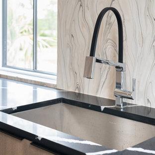 Idéer för att renovera en mycket stor funkis svarta linjär svart tvättstuga enbart för tvätt, med en undermonterad diskho, släta luckor, bruna skåp, bänkskiva i kvartsit, flerfärgad stänkskydd, klinkergolv i porslin, en tvättmaskin och torktumlare bredvid varandra och svart golv