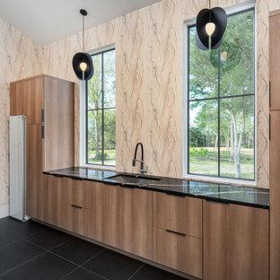 Idéer för att renovera en stor funkis l-formad tvättstuga, med en undermonterad diskho, släta luckor, skåp i mellenmörkt trä, bänkskiva i kvartsit, flerfärgad stänkskydd, fönster som stänkskydd, flerfärgade väggar, klinkergolv i porslin, en tvättmaskin och torktumlare bredvid varandra och svart golv