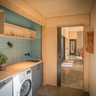 Modern inredning av ett litet parallellt grovkök, med en enkel diskho, träbänkskiva, grönt stänkskydd, stänkskydd i keramik, gröna väggar, betonggolv och grått golv