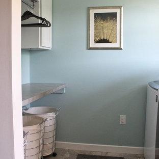 Idées déco pour une buanderie parallèle industrielle dédiée avec un placard à porte shaker, des portes de placard blanches, un plan de travail en stratifié, un mur bleu, un sol en travertin et des machines côte à côte.