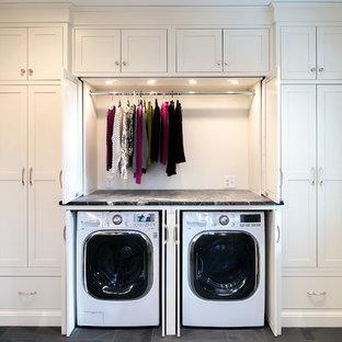 Exempel på en stor klassisk grå linjär grått tvättstuga, med skåp i shakerstil, vita skåp, bänkskiva i täljsten, skiffergolv, tvättmaskin och torktumlare byggt in i ett skåp och grå väggar
