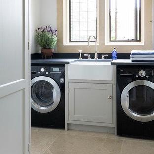 Foto di una piccola sala lavanderia moderna con lavello stile country, ante grigie, top in saponaria, pareti grigie, pavimento con piastrelle in ceramica, lavatrice e asciugatrice affiancate, pavimento beige e ante a filo