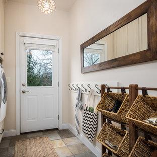 Exempel på en lantlig tvättstuga, med beige skåp, träbänkskiva och luckor med upphöjd panel