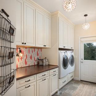 Immagine di una lavanderia country con ante beige, pareti beige, lavatrice e asciugatrice affiancate, top in legno, pavimento grigio, top marrone e ante con bugna sagomata