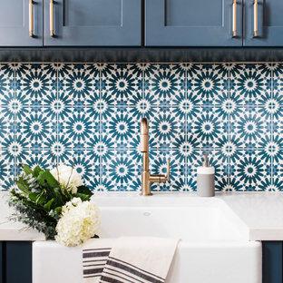 Immagine di una sala lavanderia minimalista di medie dimensioni con lavello stile country, ante in stile shaker, ante blu, top in quarzite, pareti bianche, pavimento con piastrelle in ceramica, lavatrice e asciugatrice affiancate, pavimento multicolore e top bianco