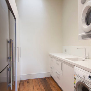 Photo of a small modern galley utility room in Sydney with an undermount sink, flat-panel cabinets, quartz benchtops, white splashback, glass sheet splashback, white cabinets, white walls, medium hardwood floors and a stacked washer and dryer.