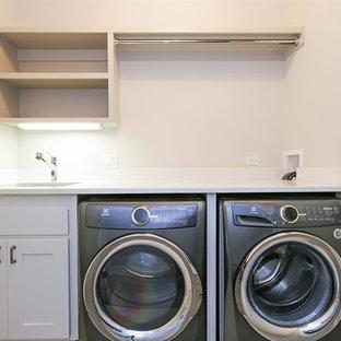 Idee per una piccola lavanderia moderna con lavello sottopiano, ante in stile shaker, ante grigie, top in quarzo composito, pareti grigie, parquet chiaro e lavatrice e asciugatrice affiancate