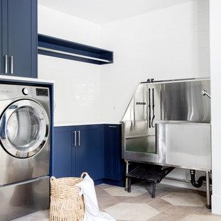 Inspiration för stora maritima l-formade vitt grovkök, med luckor med infälld panel, blå skåp, vitt stänkskydd, stänkskydd i porslinskakel, vita väggar, klinkergolv i porslin, en tvättmaskin och torktumlare bredvid varandra och brunt golv