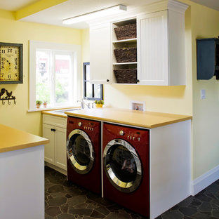 Example of a small eclectic galley vinyl floor utility room design in Vancouver with a drop-in sink, shaker cabinets, white cabinets, laminate countertops, yellow walls, a side-by-side washer/dryer and yellow countertops