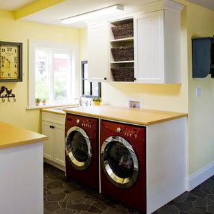 Imagen de lavadero multiusos y de galera, bohemio, pequeño, con fregadero encastrado, armarios estilo shaker, puertas de armario blancas, encimera de laminado, paredes amarillas, suelo vinílico, lavadora y secadora juntas y encimeras amarillas