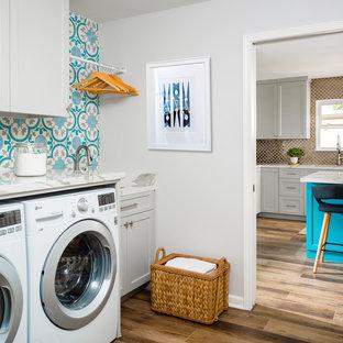 Bild på en liten vintage vita linjär vitt tvättstuga enbart för tvätt, med en undermonterad diskho, skåp i shakerstil, grå skåp, bänkskiva i koppar, grå väggar, klinkergolv i porslin, en tvättmaskin och torktumlare bredvid varandra och brunt golv
