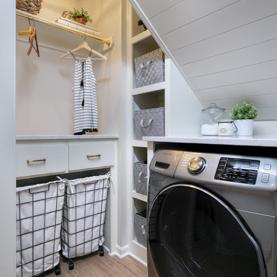 Dedicated laundry room - cottage medium tone wood floor and brown floor dedicated laundry room idea in Kansas City with open cabinets, white cabinets, white walls and white countertops