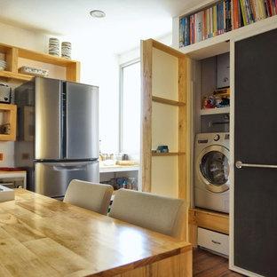 Esempio di un piccolo ripostiglio-lavanderia tropicale con lavello da incasso, ante con bugna sagomata, ante in legno chiaro, top in legno, pareti bianche, pavimento in legno massello medio e lavatrice e asciugatrice nascoste