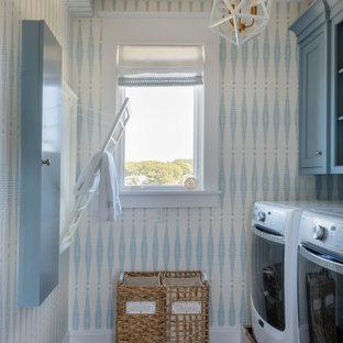 Idées déco pour une buanderie linéaire bord de mer dédiée avec un placard à porte affleurante, des portes de placard bleues, un mur bleu, un sol en bois foncé et un sol marron.