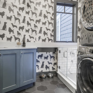 Inspiration for a mid-sized transitional l-shaped porcelain floor utility room remodel in Seattle with an undermount sink, shaker cabinets, blue cabinets, quartz countertops, gray walls and a stacked washer/dryer