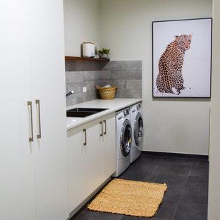 Idee per una grande sala lavanderia minimal con lavello a doppia vasca, ante bianche, top in laminato, paraspruzzi grigio, paraspruzzi in gres porcellanato, pareti bianche, pavimento in gres porcellanato, lavatrice e asciugatrice affiancate, pavimento grigio e top bianco