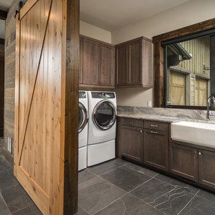 Idee per una sala lavanderia stile rurale con lavello stile country, ante in stile shaker, ante in legno bruno, pareti beige, lavatrice e asciugatrice affiancate, pavimento grigio e top grigio