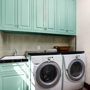 Example of a mid-sized tuscan single-wall terra-cotta tile and brown floor laundry room design in Los Angeles with raised-panel cabinets, blue cabinets, white walls, a side-by-side washer/dryer, quartz countertops and black countertops