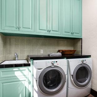 Foto di una lavanderia mediterranea di medie dimensioni con ante con bugna sagomata, ante blu, pareti bianche, pavimento in terracotta, lavatrice e asciugatrice affiancate, pavimento marrone, top in quarzo composito e top nero