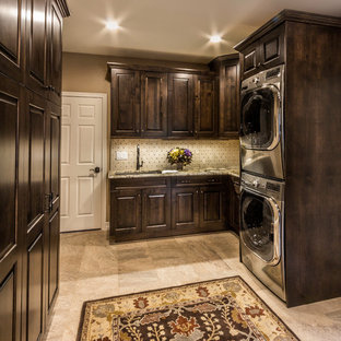 Design ideas for a large traditional utility room in Denver with an undermount sink, dark wood cabinets, granite benchtops, porcelain floors and a stacked washer and dryer.