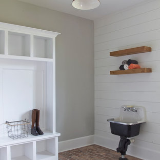 Lantlig inredning av ett mellanstort grovkök, med öppna hyllor, vita skåp, grå väggar, tegelgolv, rött golv och en allbänk