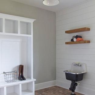 Exemple d'une buanderie nature multi-usage et de taille moyenne avec un placard sans porte, des portes de placard blanches, un mur gris, un sol en brique, un sol rouge et un évier utilitaire.